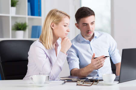 Young office workers looking at laptop screen