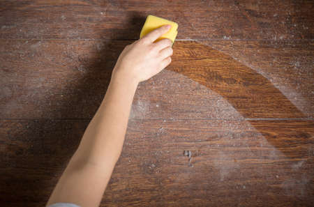 Met behulp van gele spons voor het schoonmaken van stoffige hout