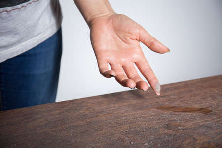 Close-up of dust on woman finger taken from wooden table Stock Photo