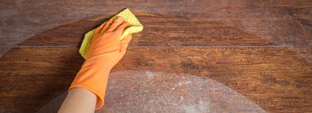 soiled: Cleaning soiled parquet in gloves with yellow rag