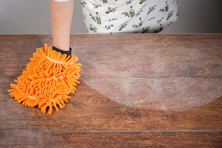 sanitizing: Woman cleaning dusty table with orange cleaner