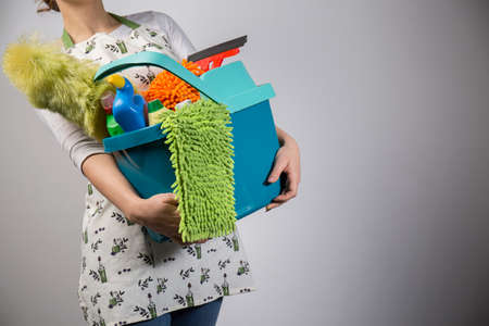 house maid: Housewife holding all of her cleaning tools Stock Photo