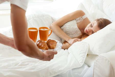 enamorados en la cama: Hombres trae el desayuno a la cama de su novia durmiendo