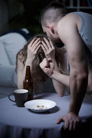beaten woman: Violent man threatening with fist to his broken down girlfriend Stock Photo
