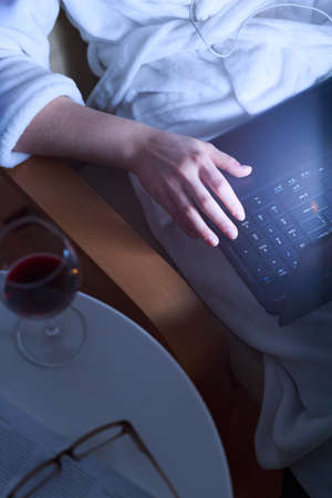 net surfing: Lonely girl surfing the net and drinking wine