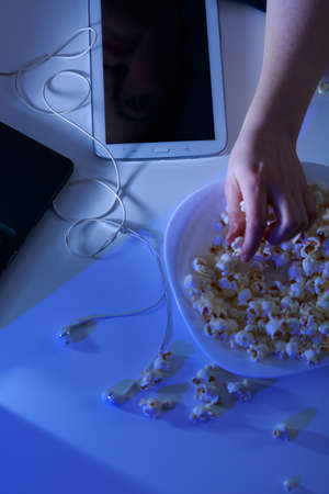 addicted: Woman addicted to modern technology and popcorn