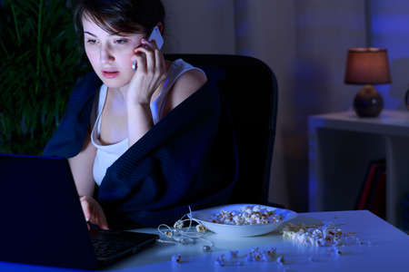 addicted: Young woman addicted to computer and phone Stock Photo