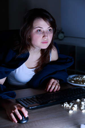 sleeplessness: Girl suffering from sleeplessness surfing on the internet