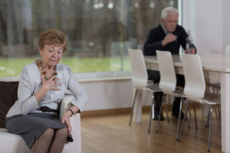 distraught: Aged distraught woman and her alcoholic husband Stock Photo