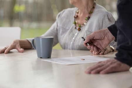 高齢者男性の離婚の書類に署名のクローズ アップ