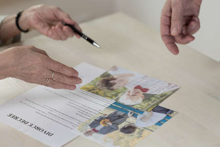 Close-up of betrayed older woman signing divorce decree