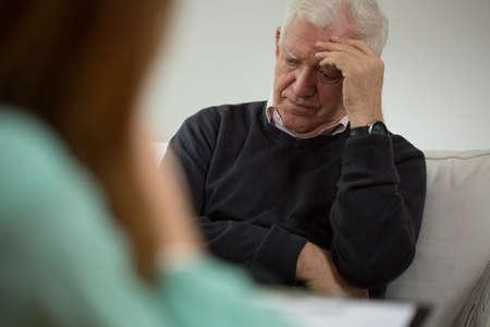 Oude man op bezoek in het kantoor van psychiater Stockfoto