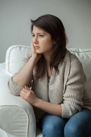 Worried young girl sitting alone and thinking Imagens