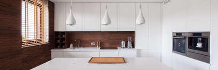 Panorama of white and brown kitchen interior