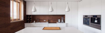 Panorama of white and brown kitchen interior