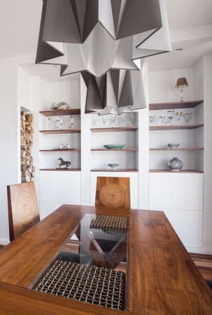 Designed pendant and wooden table in modern interior photo