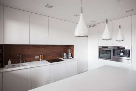 White cupboards and worktop in luxury kitchen
