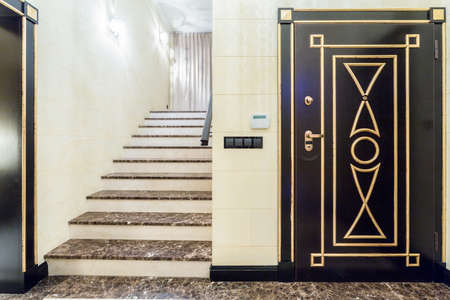 Wide marble stairs in fancy entrance hall with black door photo