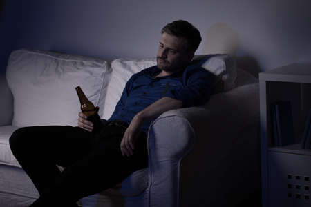 Unemployed man sitting on the sofa and drinking beer