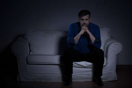 Lonely despair man sitting in dark room