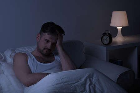 sleeplessness: L'uomo soffre di insonnia seduto sul letto