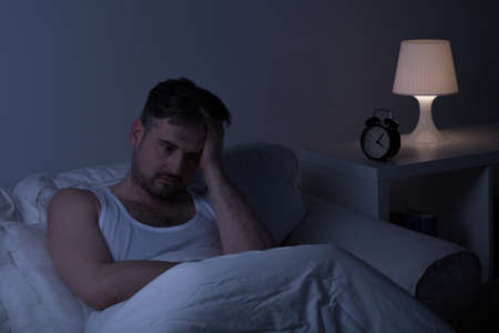 Man suffering from sleeplessness sitting in the bed Stock Photo