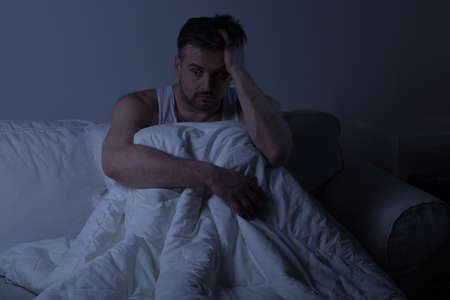despairing: Mature man with insomnia sitting in the bed Stock Photo