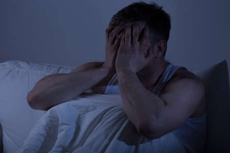 sleepless: Image of despair man covering his face