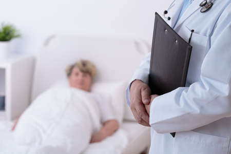 Doctor and senior patient in hospital room photo