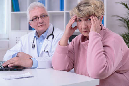 despairing: Senior woman with migraine in doctors office