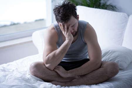 dolor de cabeza: Hombre soñoliento joven agotado en la mañana Foto de archivo