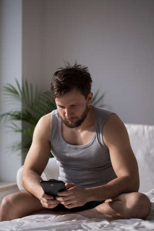 in pajama: Young handsome man in pajama using tablet in bed Stock Photo
