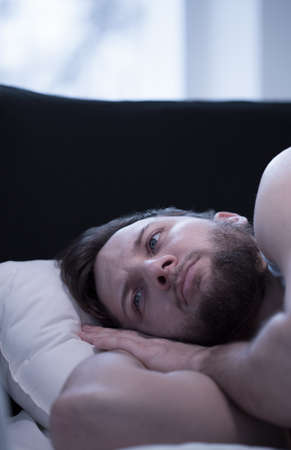 Close-up of young wake up man trying to fall asleep photo
