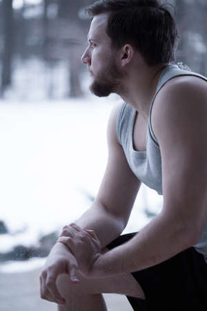 Vertical view of young attractive man sitting alone photo