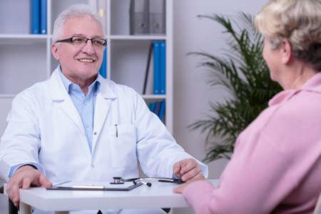 uniformes de oficina: Una m�s vieja mujer que tiene consulta m�dica en el consultorio m�dico