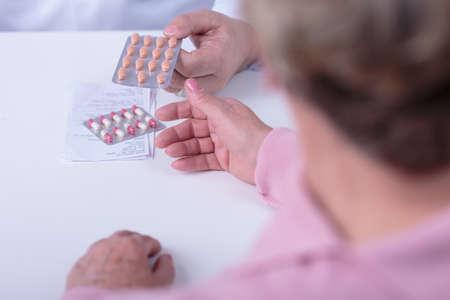 Close-up of doctors hands giving prescription and medicament photo