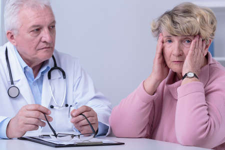 woeful: Image of worried senior woman in doctors office Stock Photo