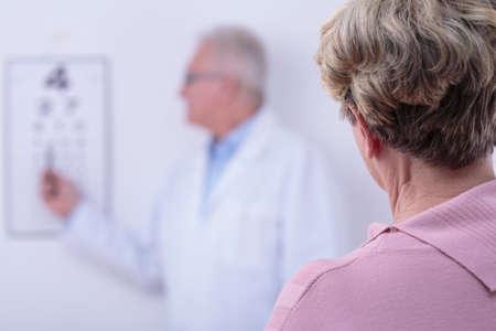 myopia: Senior woman with cataract in opticians office