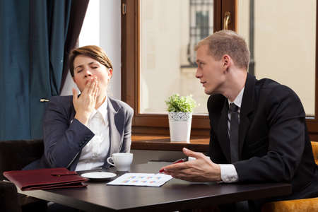 yawning: Businesswoman yawning during meeting in the cafe Stock Photo