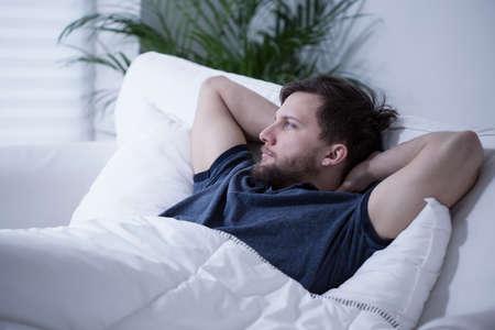 enfermos: Hombre hermoso joven tumbado en la cama por días