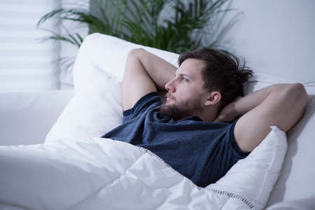 rest day: Young handsome man lying in bed at day Stock Photo