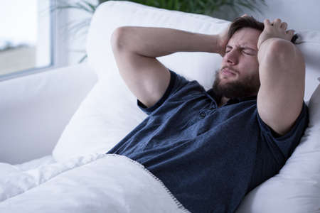sleeplessness: Young handsome sleepy man with headache lying in bed Stock Photo