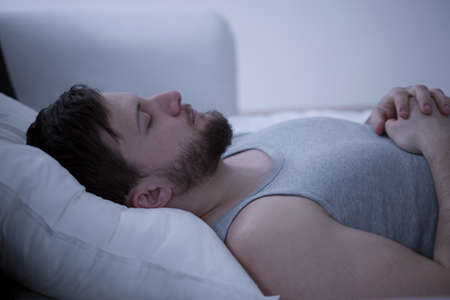 Close-up of young handsome man dozing in bed
