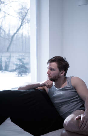 Young attractive man looking through the window in the morning photo