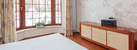 Panoramic view of bright bedroom with huge window photo