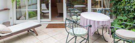 Elegant veranda with designed garden furniture an ivy - panorama photo