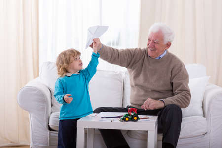 kindergartner: Grandpa and little boy playing with paper airplane Stock Photo