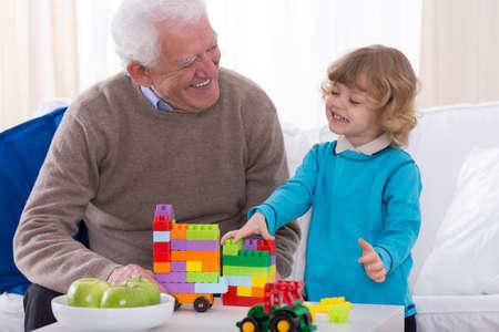 kindergartner: Grandpa and preschooler playing with building blocks
