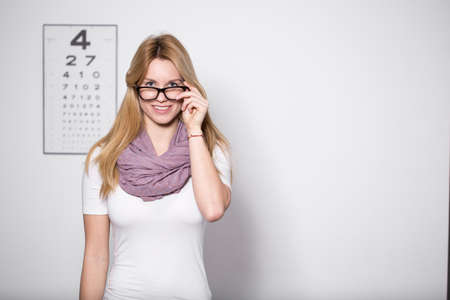 hyperopia: Young beautiful woman with glasses at opticians office