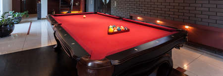 billiards room: Panoramic view of red pool table in a luxurious interior
